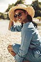 Portrait of happy woman wearing straw hat and sun glasses on the beach - SUF00160