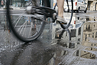 Riding bicycle in the city on a rainy day, partial view - ZMF00481