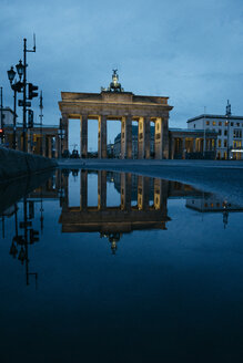 Germany, Berlin, view to  Brandenburg Gate reflecting in puddle by night - ZMF00484
