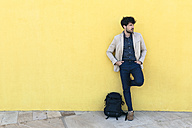 Young man with backpack standing  in front of yellow wall - GIOF02871