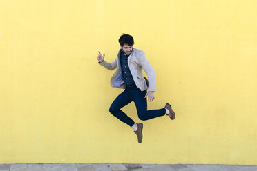 Young man jumping in the air in front of yellow wall - GIOF02874