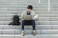 Pensive man with laptop sitting on steps checking documents - GIOF02886
