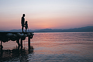Italy, Lazise, father and little daughter standing on jetty looking at Lake Garda at sunset - IPF00394