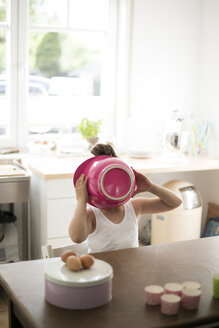 Little girl in kitchen covering her face with pink mixing bowl - MOEF00023