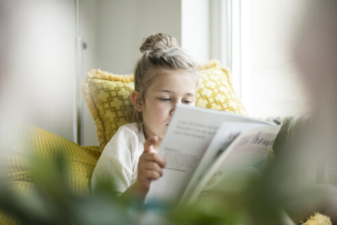 Portrait of relaxed little girl sitting on armchair reading magazine - MOEF00050