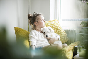 Little girl sitting on armchair at home cuddling with her dog - MOEF00053