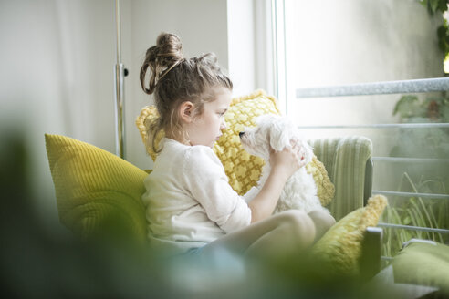 Little girl sitting on armchair with her dog - MOEF00056