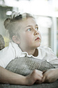 Portrait of serious little girl looking out of window - MOEF00059