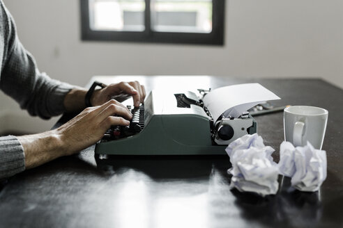 Close-up of man using typewriter with crumpled paper on desk - GIOF02890