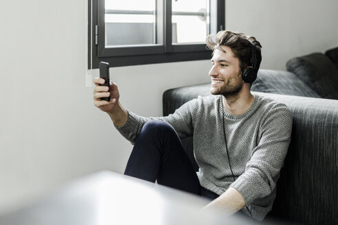 Smiling young man with cell phone and headphones at home - GIOF02896