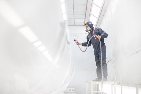 Industrial worker spray painting and wearing protective clothing - ZEF14059