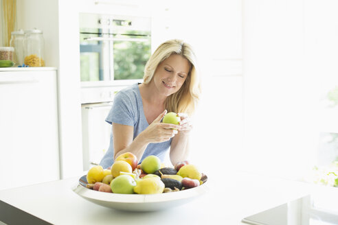 Smiling woman at home taking apple from fruit bowl - MAEF12242