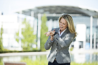 Happy businesswoman using smartwatch outdoors - MAEF12243