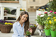 Young woman buying potted flowers - CHAF01890