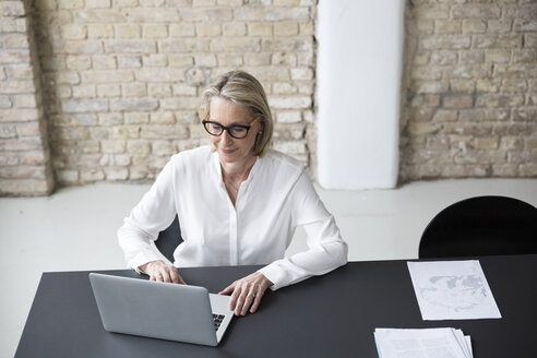 Mature businesswoman working in office - RBF05747