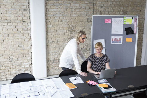 Mature businesswoman working with younger colleague in office - RBF05750