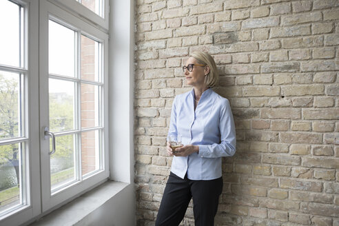 Mature businesswoman looking out of window, holding cup of coffee - RBF05768