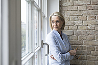 Mature businesswoman standing at window, looking worried - RBF05771