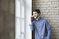 Young businessman standing at window, using smartphone - RBF05804