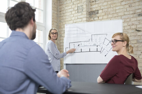 Mature businesswoman explaining floor plan to colleagues - RBF05810