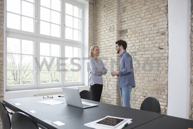 Mature businesswoman working with younger colleague in office - RBF05813