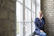 Businesswoman sitting on window sill, making a call - RBF05831