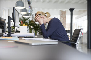 Businesswoman working in office, being stressed out - RBF05834