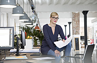 Businesswoman sitting on desk, holding papers - RBF05837