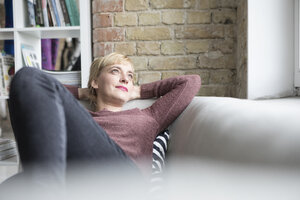 Woman relaxing on couch at home - RBF05840