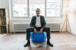 Senior businessman sitting on fitness ball - GUSF00001