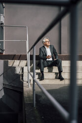 Senior businessman sitting on concrete stairs - GUSF00016