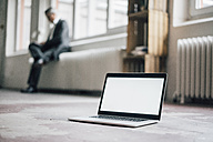 Laptop on floor with businessman in background - GUSF00034