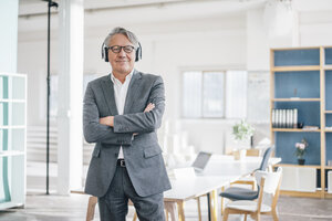 Senior businessman listening to music with headphones in office - GUSF00037