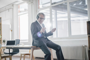 Happy senior businessman listening to music with headphones in office - GUSF00040