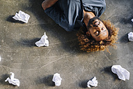 Man lying on the floor surrounded by crumpled paper - KNSF01707