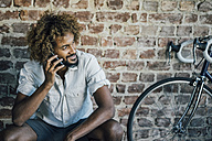 Smiling young man with bicycle on cell phone - KNSF01719