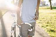 Close-up of man with bicycle checking cell phone - KNSF01728