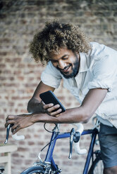 Happy young man with bicycle checking cell phone - KNSF01740