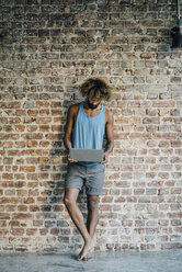 Man with beard and curly hair using laptop at brick wall - KNSF01743