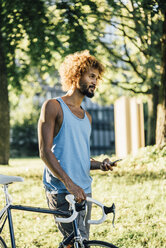 Young man with bicycle and cell phone in park - KNSF01746