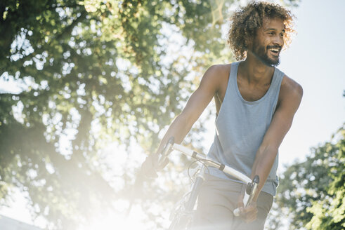 Happy young man with bicycle in park - KNSF01749