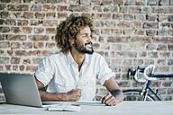 Smiling young man at desk thinking - KNSF01755
