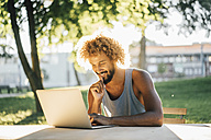 Man with beard and curly hair using laptop at table in park - KNSF01758