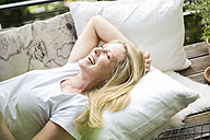 Laughing blond woman relaxing on balcony - MAEF12254