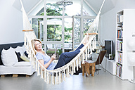 Smiling blond woman with tablet relaxing in hammock in the living room - MAEF12257