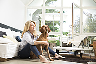Relaxed woman sitting with her dog on floor of the living room - MAEF12263