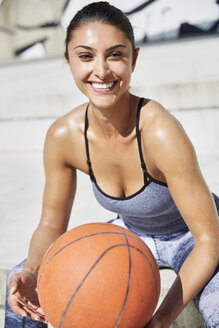 Portrait of smiling woman holding basketball outdoors - SUF00184