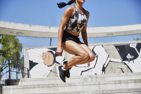 Fit woman jumping outdoors - SUF00193
