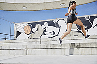 Fit woman running outdoors - SUF00196