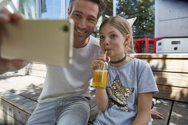 Happy father and daughter taking a selfie at an outdoor cafe - SUF00211